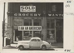 Following evacuation orders, this store, at 13th and Franklin Streets, was closed. The owner, a University of California graduate of Japanese descent, placed the I AM AN AMERICAN sign on the store front on December 8, the day after Pearl Harbor. Evacuees of Japanese ancestry will be housed in War Relocation Authority centers for the duration. -- Photographer: Lange, Dorothea -- Oakland, California. March 13, 1942.  BANC PIC 1967.014 v.56 GA-35—PIC