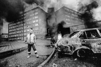Young boy holding pipe near burning car in front of the Divis flats in Belfast,