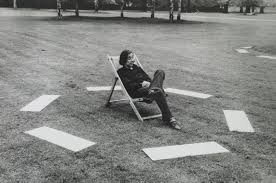 Conceptual art, man in chair on grass surrounded by white rectangles