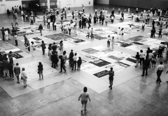 AIDS memorial quilt laid out in groupings on the floor as dozens of people walk around and look at them, 1989