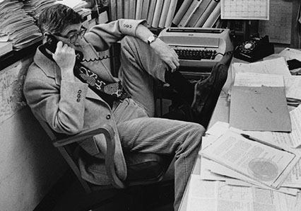 Bruce Ames at his desk, foot up, talking on phone, surrounded by papers and books