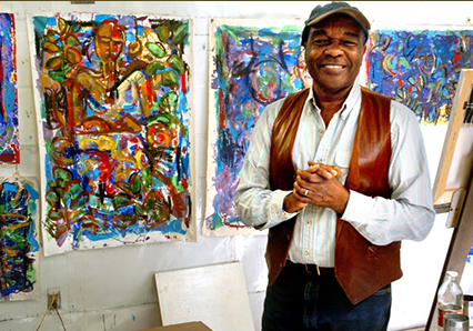 David C. Driskell in art studio, with paintings behind him