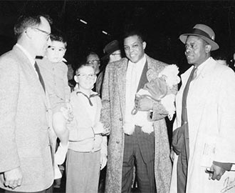 Edward Howden (left) and Willie Mays (center). Howden mediated an incident in which Mays was initially denied permission to buy a home in an all-white neighborhood in San Francisco (1957)
