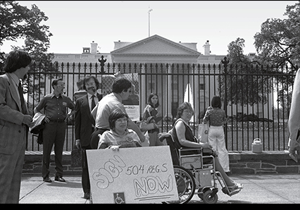 """Judy Heumann in front of White House with sign that says """"Sign 504 Reg S Now."""""""