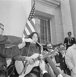 "Photo of Joan Baez singing ""We Shall Overcome"" on Sproul Hall steps before demonstrators file in for sit-in. December 2, 1964"