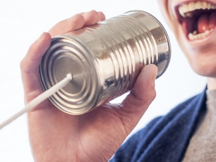 Man speaking into tin can with string